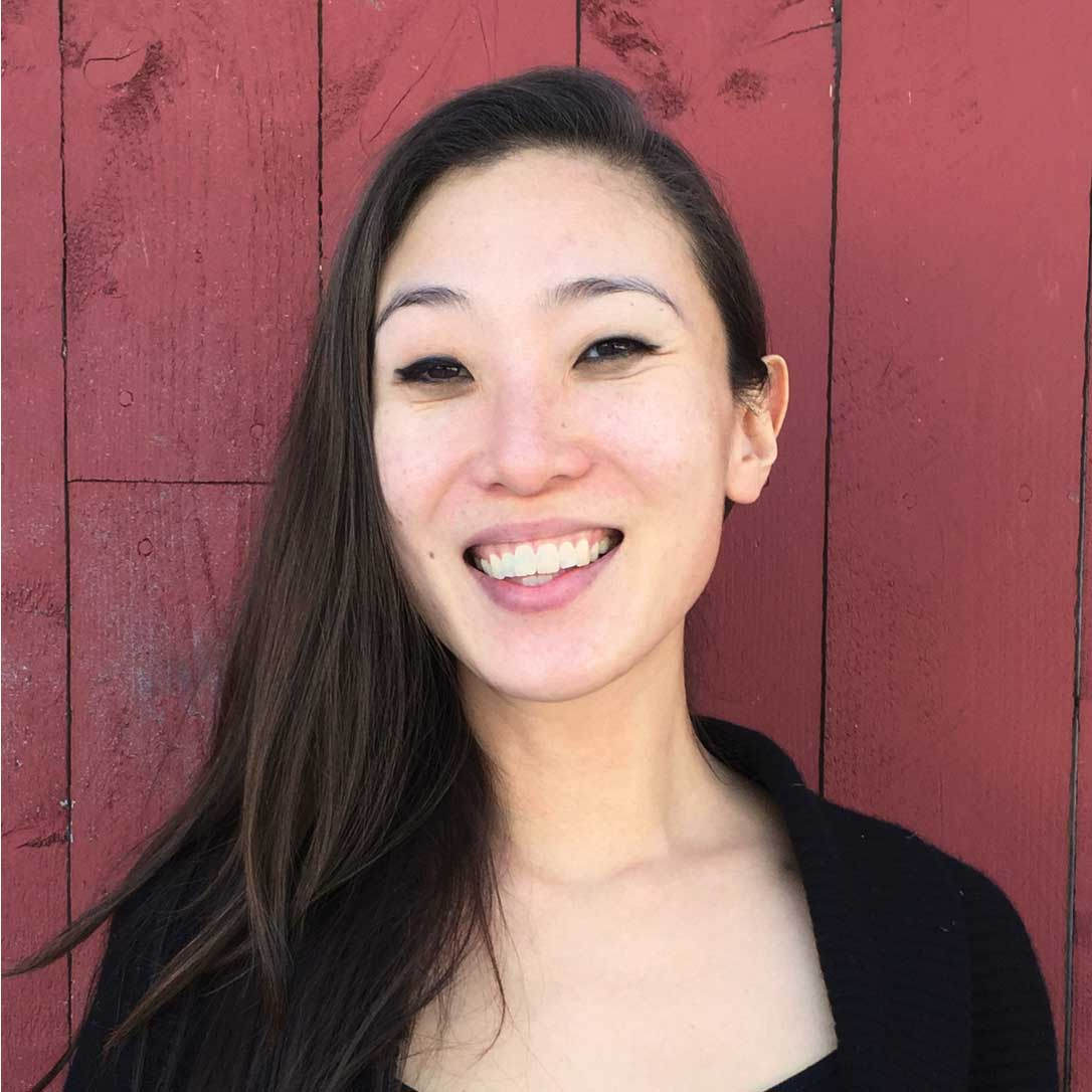 A portrait photo of Una Lee, Creative Director at And Also Too. Una is smiling towards the camera as she stands against an Alizarin crimson wooden wall.