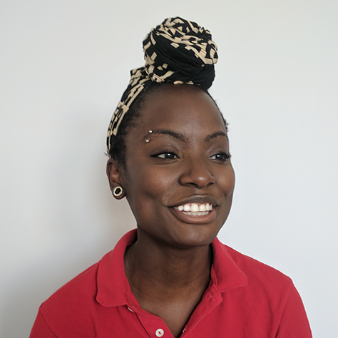 Photo: Sylver sits in front of a white wall, smiling and wearing a red shirt and black and beige hair wrap.