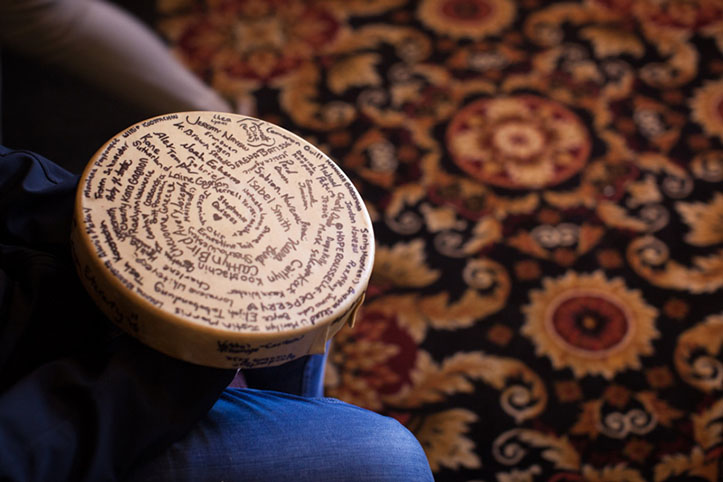 Photo: The Feathers of Hope hand drum resting on a person's knee. The drum has dozens of young First Nations people's signatures on the hide. A patterned carpet is in the background.