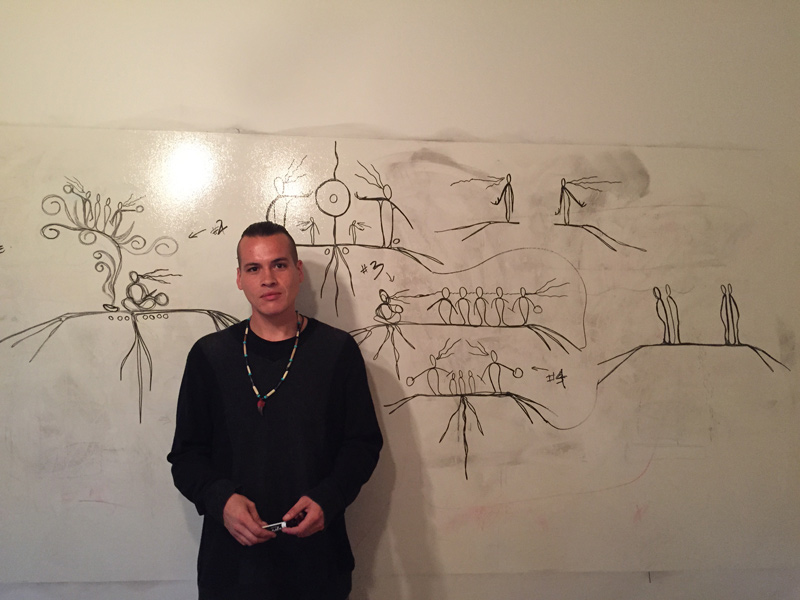 Photo: Nyle Johnston holding a marker, the Anishinaabe artist who we collaborated with to create the artwork in the Justice and Juries report. He is standing in front of a whiteboard, which is covered in sketches of the artwork for the report.