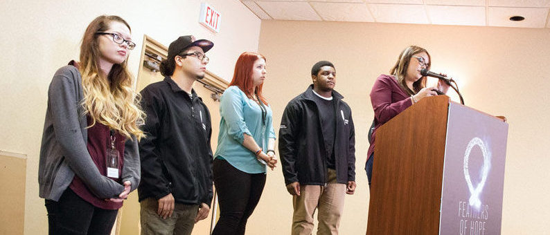 Photo: Four Youth Amplifiers and one Youth Advisor who worked on the Justice and Juries report. The youth on the far right hand side is at a podium speaking into a microphone while the other four youth stand behind the podium.
