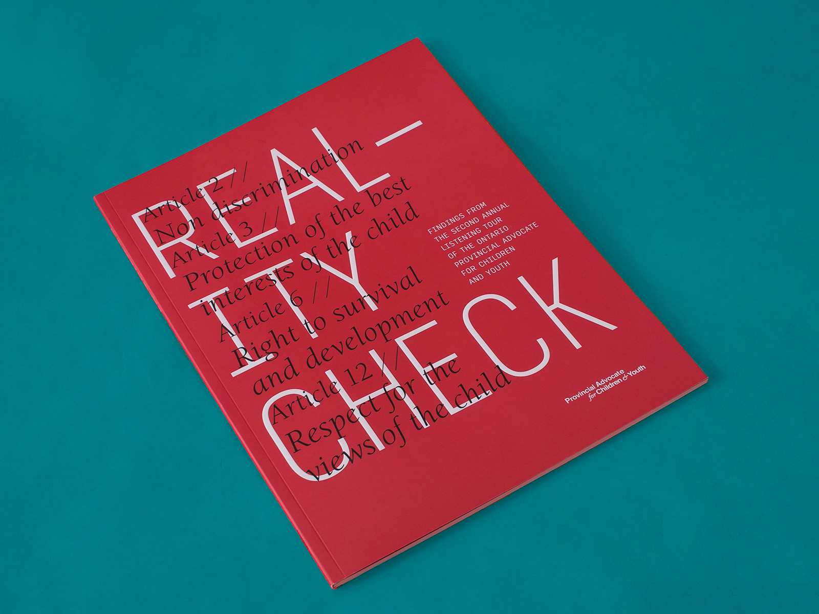 A photograph of the Listening Tour Report cover taken on a teal background. The cover background is printed red, there are lines of black italic text that span over the large white capital letters of the title. This takes up most of the page. There is additional text in much smaller font at both the middle and the bottom of the right side of the cover.