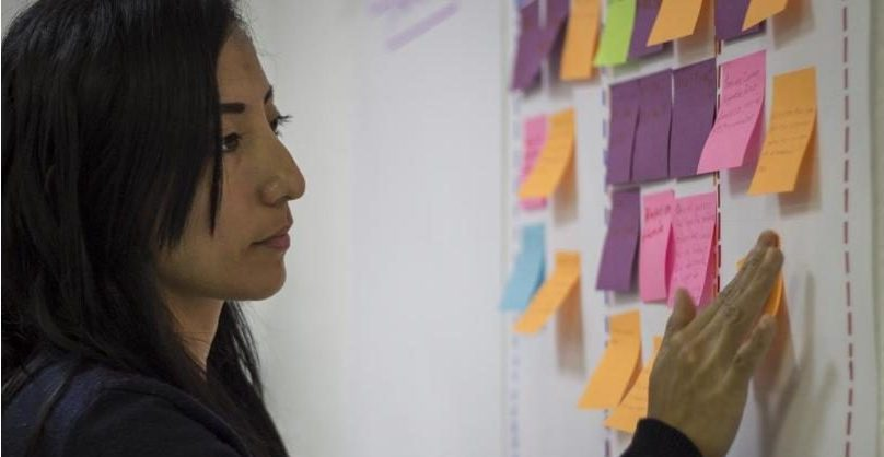 person standing before a whiteboard covered in colorful post-its. The person is adding a new post-it to the board with a contemplative, focused expression.