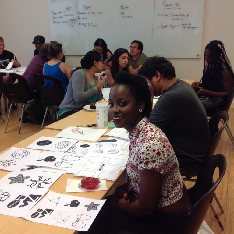 Photograph of a group designing with one person facing the camera and smiling in foreground