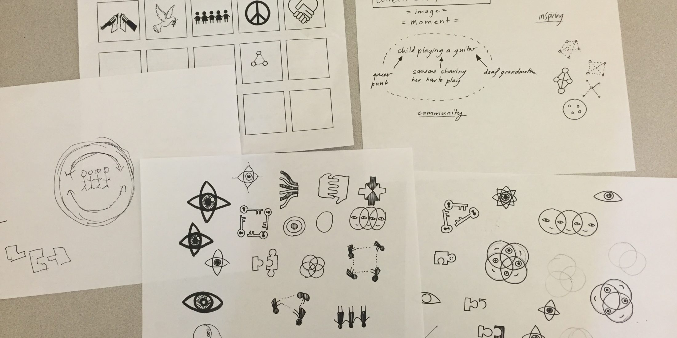 Photo: Five sheets of paper sitting on a table. One of the sheets is an exercise sheet to generate different types of icons. The other four are filled with pencil sketches and notes for new designs.