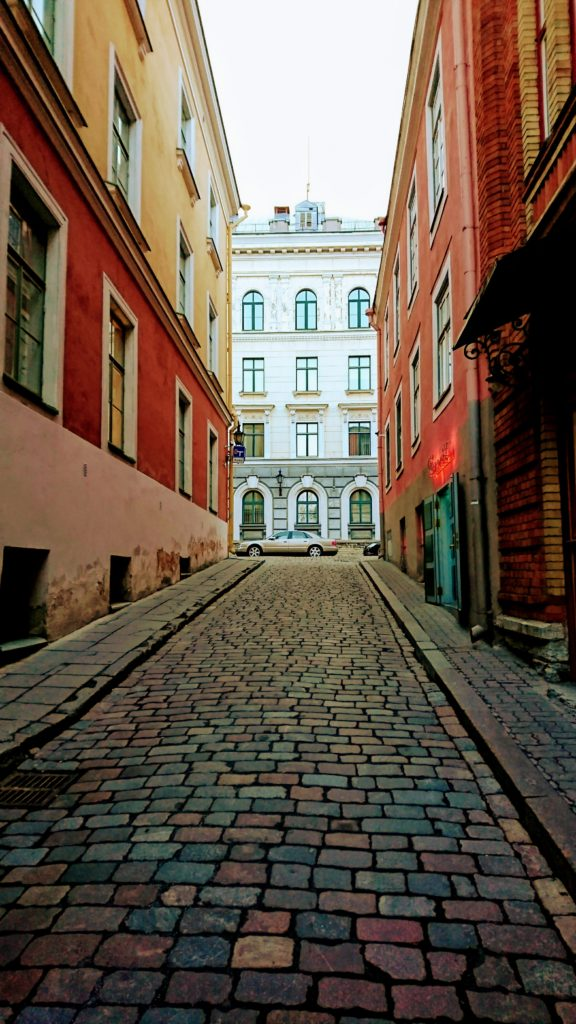 Photo: A European, multi-coloured, cobblestone, alleyway, lined with multi coloured buildings with white window frames. There is a car at the end of the alley and white building adding to the windows. The sky above is a light gray.