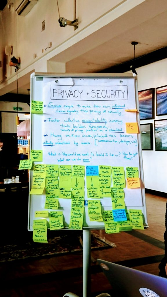 A photograph of a newsprint chart. The title reads 'PRIVACY + SECURITY', it is written in black and is outlined by a rectangle. Points below are written in a bright light blue text with, the keywords underlined in dark blue. There are a few post-its at the top of the chart paper and numerous post-its stuck to the bottom