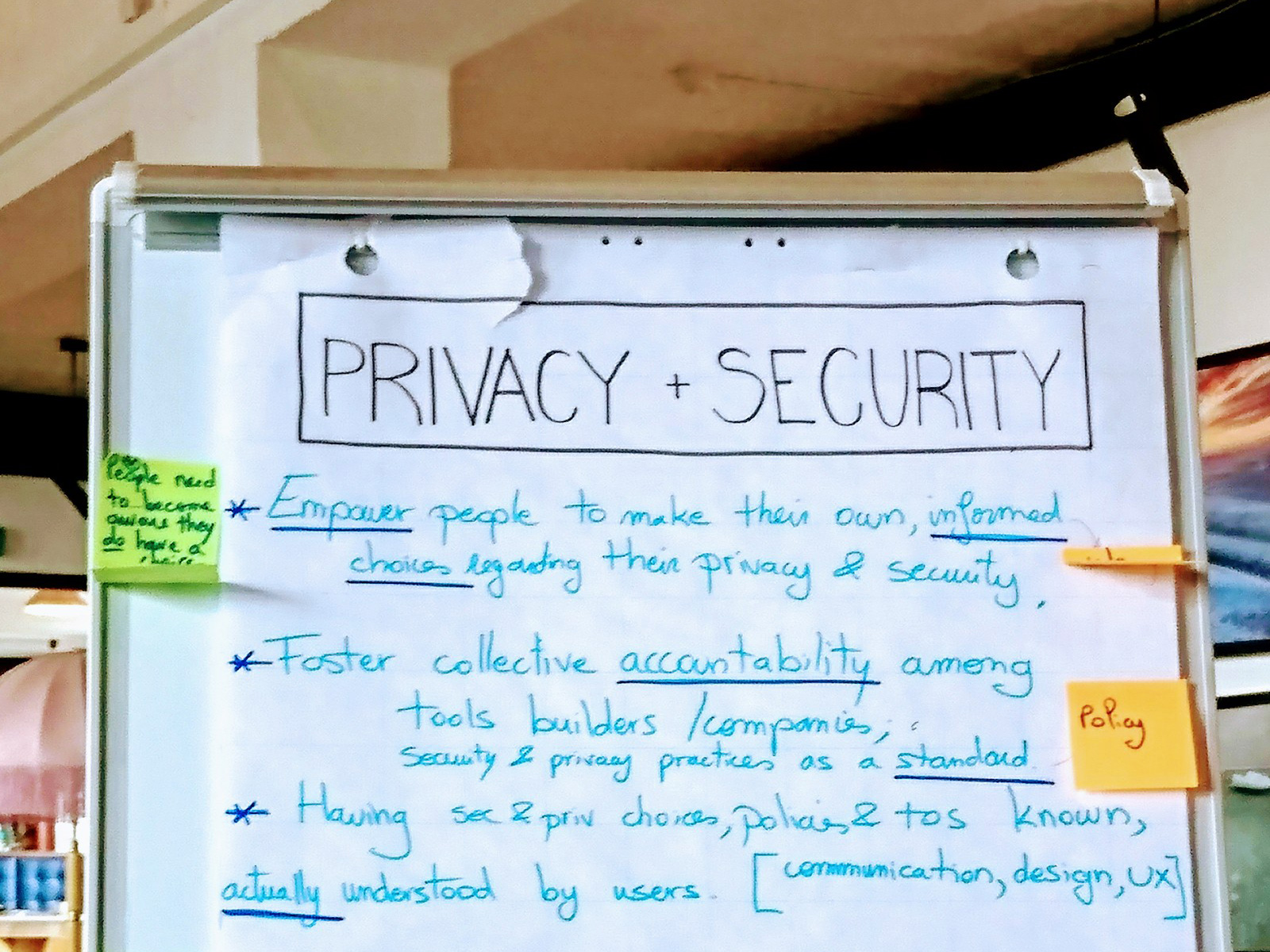 A photograph of part of a newsprint chart. The title reads 'PRIVACY + SECURITY', it is written in black and is outlined by a rectangle. There are 3 points written in a bright light blue text with, the keywords are underlined in dark blue.