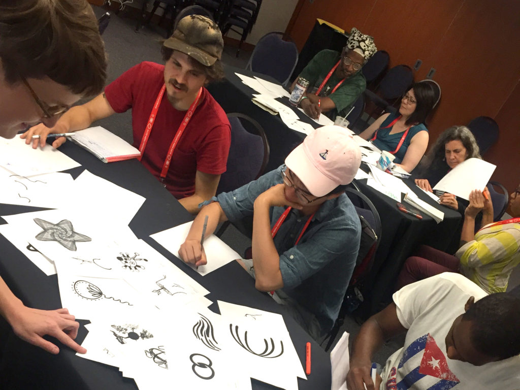 Several people sit at tables, sketching on pieces of paper. In front of them are printouts of icson from the Vision Archive representing concepts like empathy, unity, and more. Some icons are geometric and digital looking, while others have a more hand drawn aesthetic.