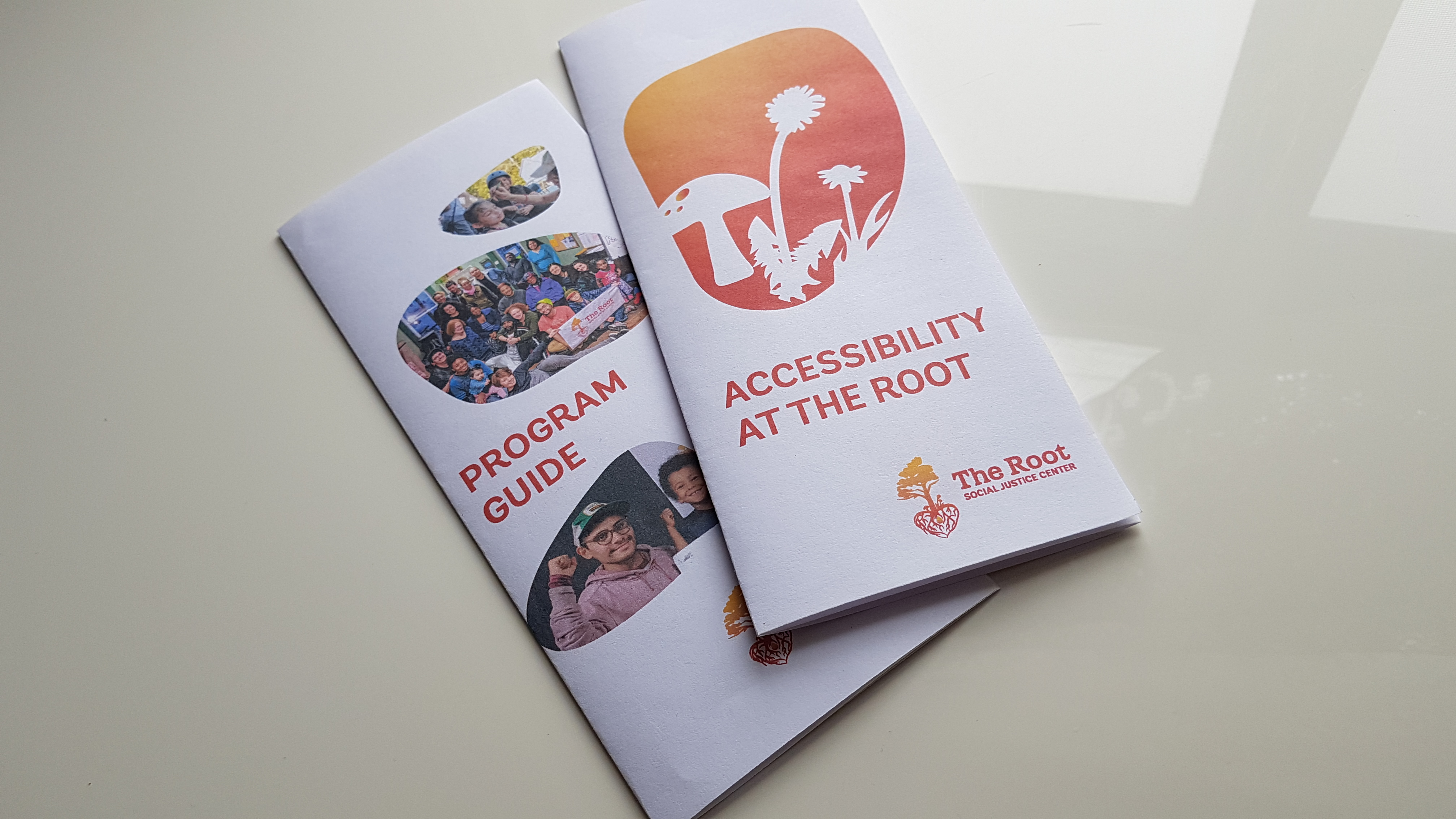 "Photo: Two folded brochures sit on a white surface, one stacked on the other. The top brochure reads ""Accessibility at The Root"" and has silhouettes of a toadstool and dandelions against a gradient gold to red background, inside a rock-shaped frame. In the bottom right hand corner is The Root logo. The one below it reads ""Program Guide"" and has 3 photos of various people, mainly people of colour, inside of rock shaped frames."