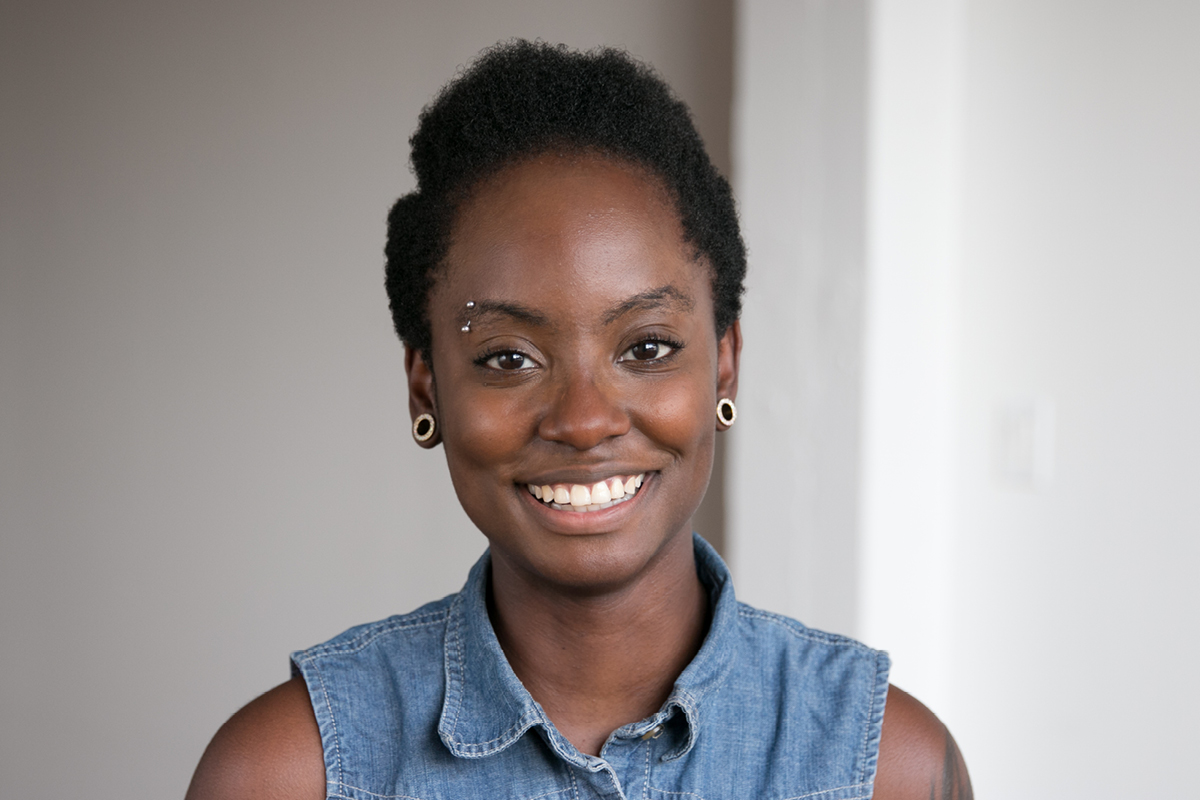 Photo: A headshot of Sylver Sterling, Designer at And Also Too. She is smiling and wearing a denim shirt.