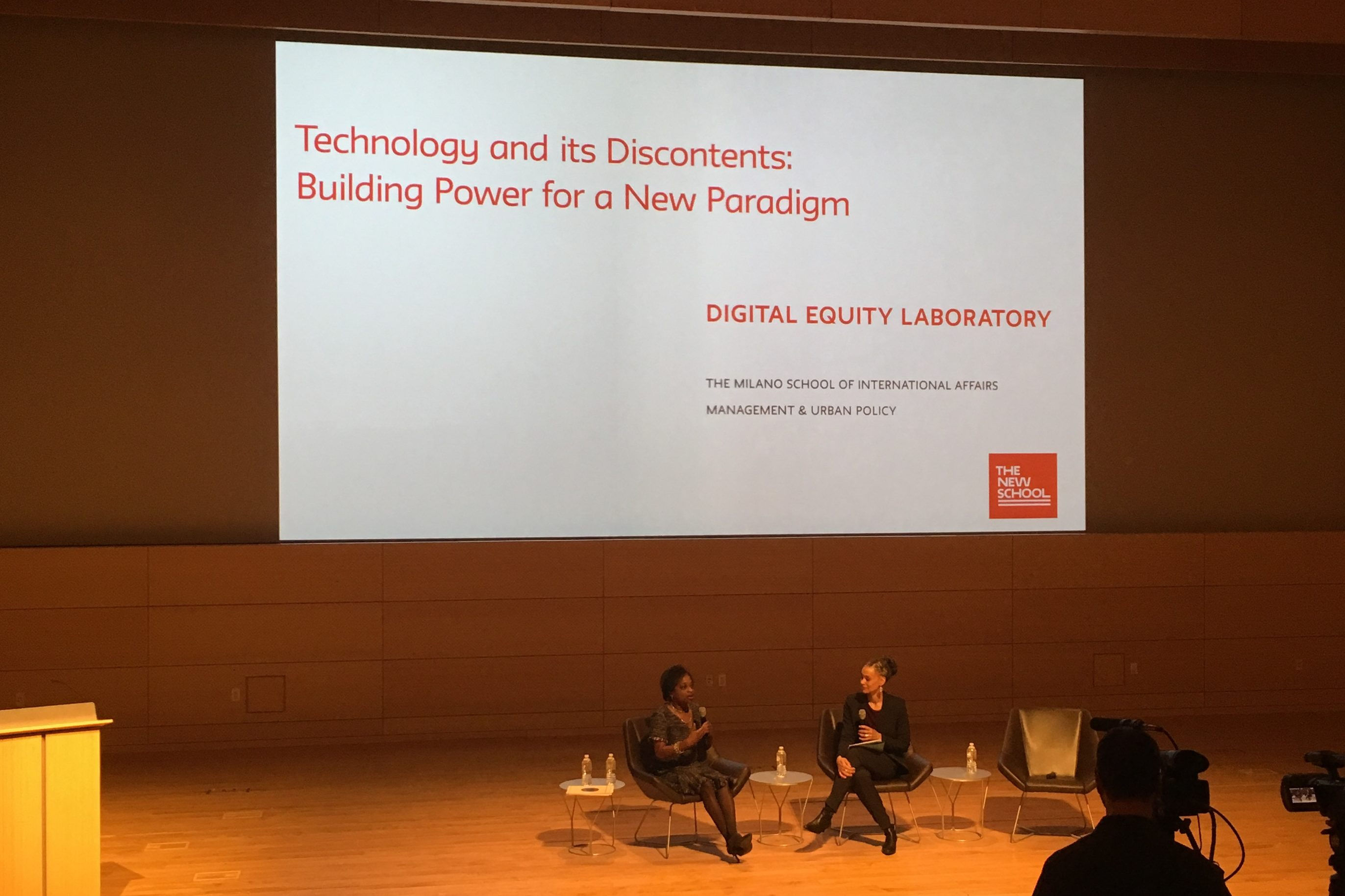 "Two African American women are seated and in conversation on a stage. Behind them is a large white screen with the title of the event, ""Technology and its Discontents: Building Power for a New Paradigm"" in orange."