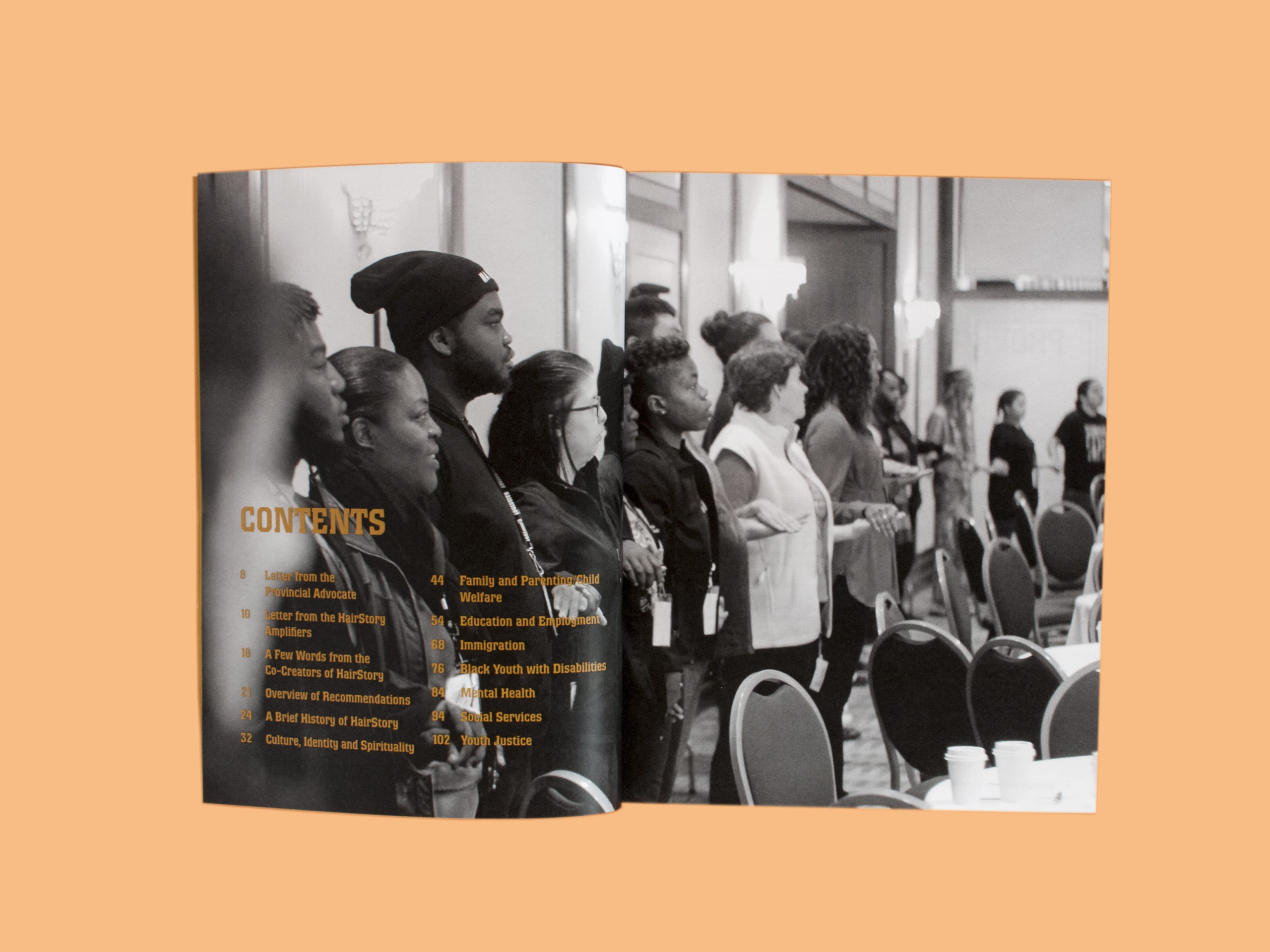 Photo of the contents spread from HairStory—Rooted. Behind the table of contents is a large photograph of many people standing in a circle, holding hands. Most of the people are Black youth, and they stand alongside elders and allies.