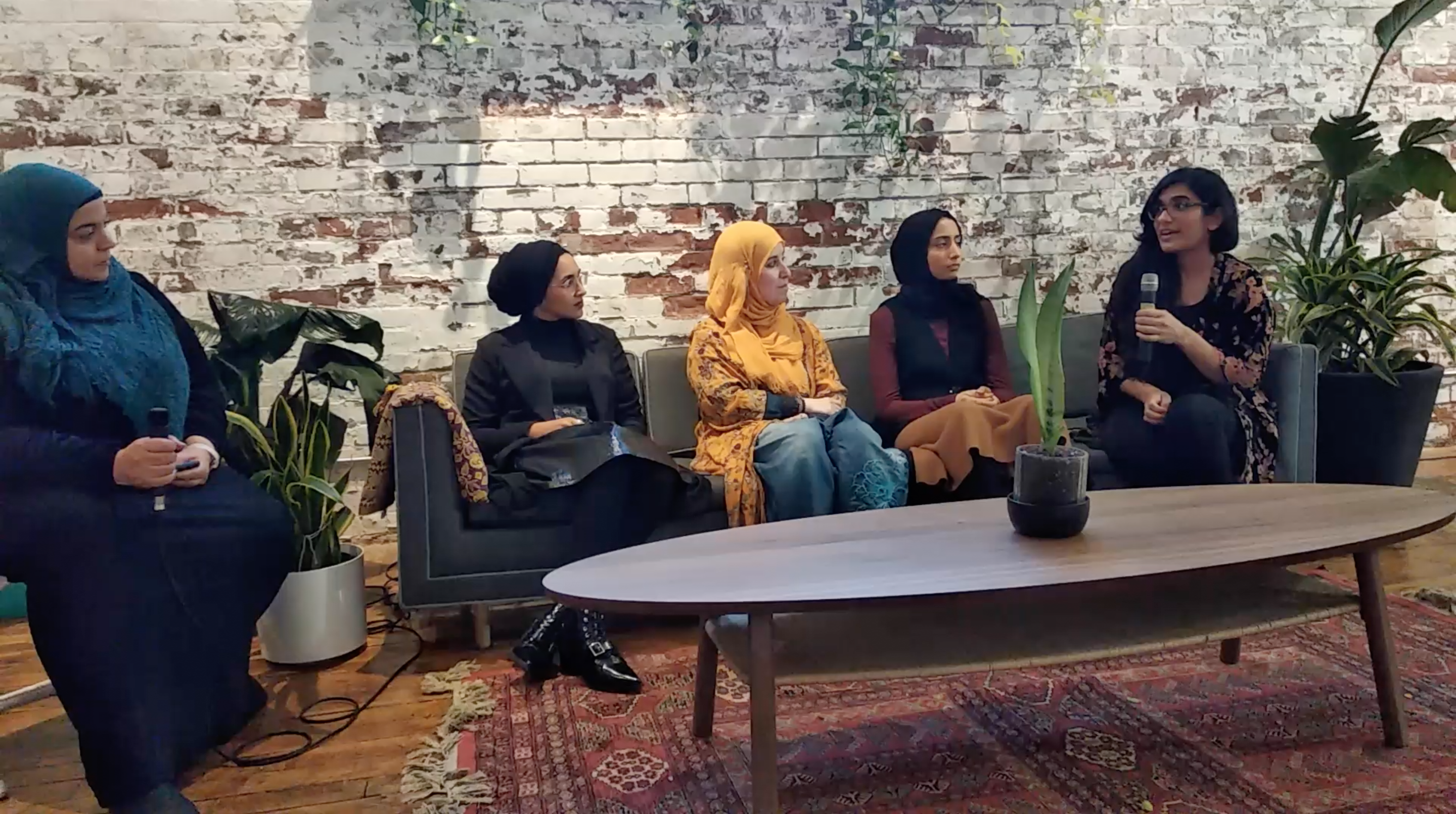 A photograph of 5 people- a moderator and four panelits. The moderator sits on a chair to the left of the photo and four panelists sit on a couch to the right side of the image. The space has a living room feel with a washed brick wall backdrop, there are plants in the space, a warm rug, and a coffee table and plants.