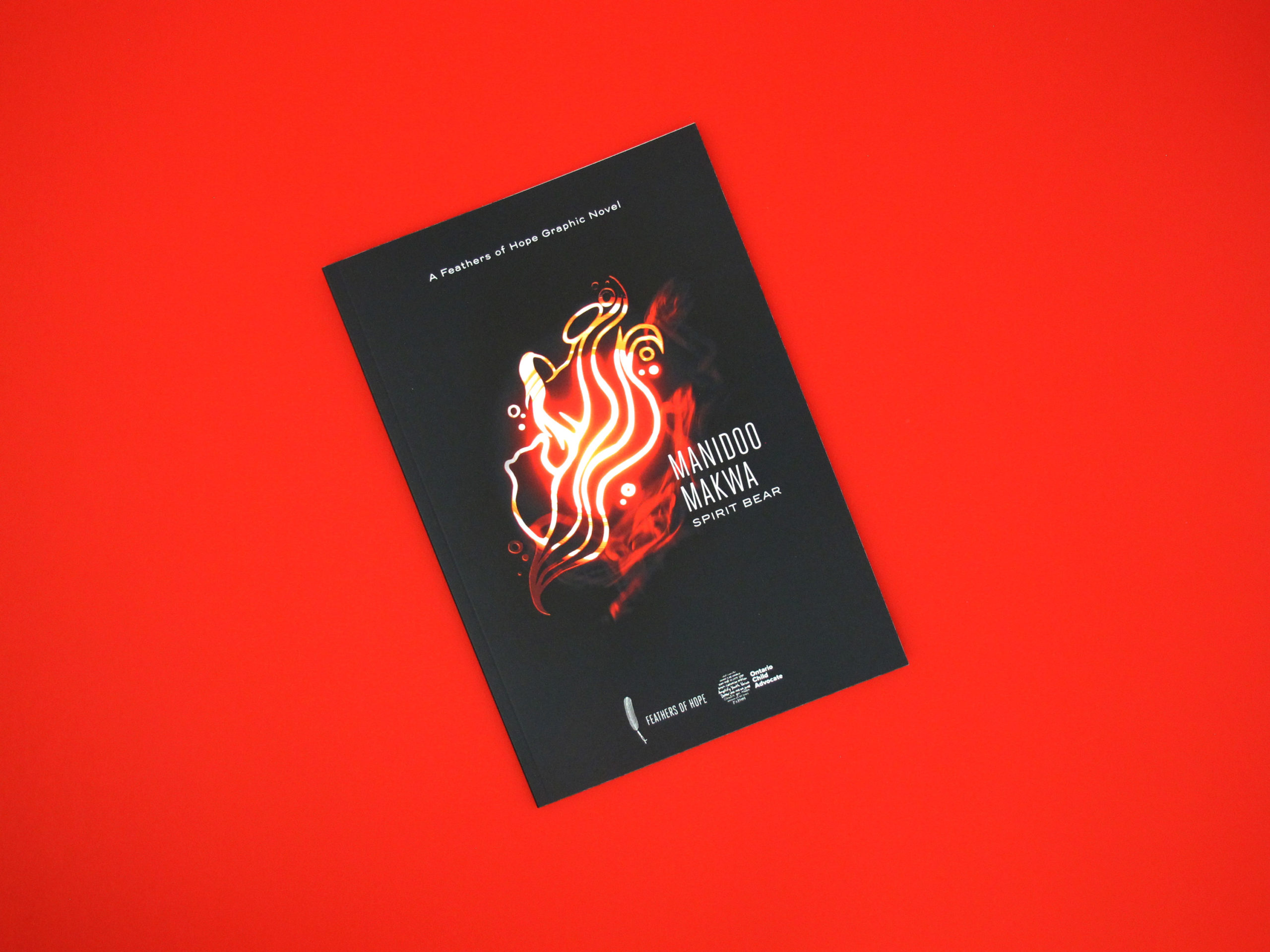 Photo shows the front cover of the graphic novel Manidoo Makwa: Spirit Bear. It is a black cover with a glowing, red illustration in the center. The illustration shows an undulating path moving upwards. On the path we can distinguish a bear standing behind the silhouette of a young person holding a drum. They seem to be flowing along with the path, as if they were one with it.