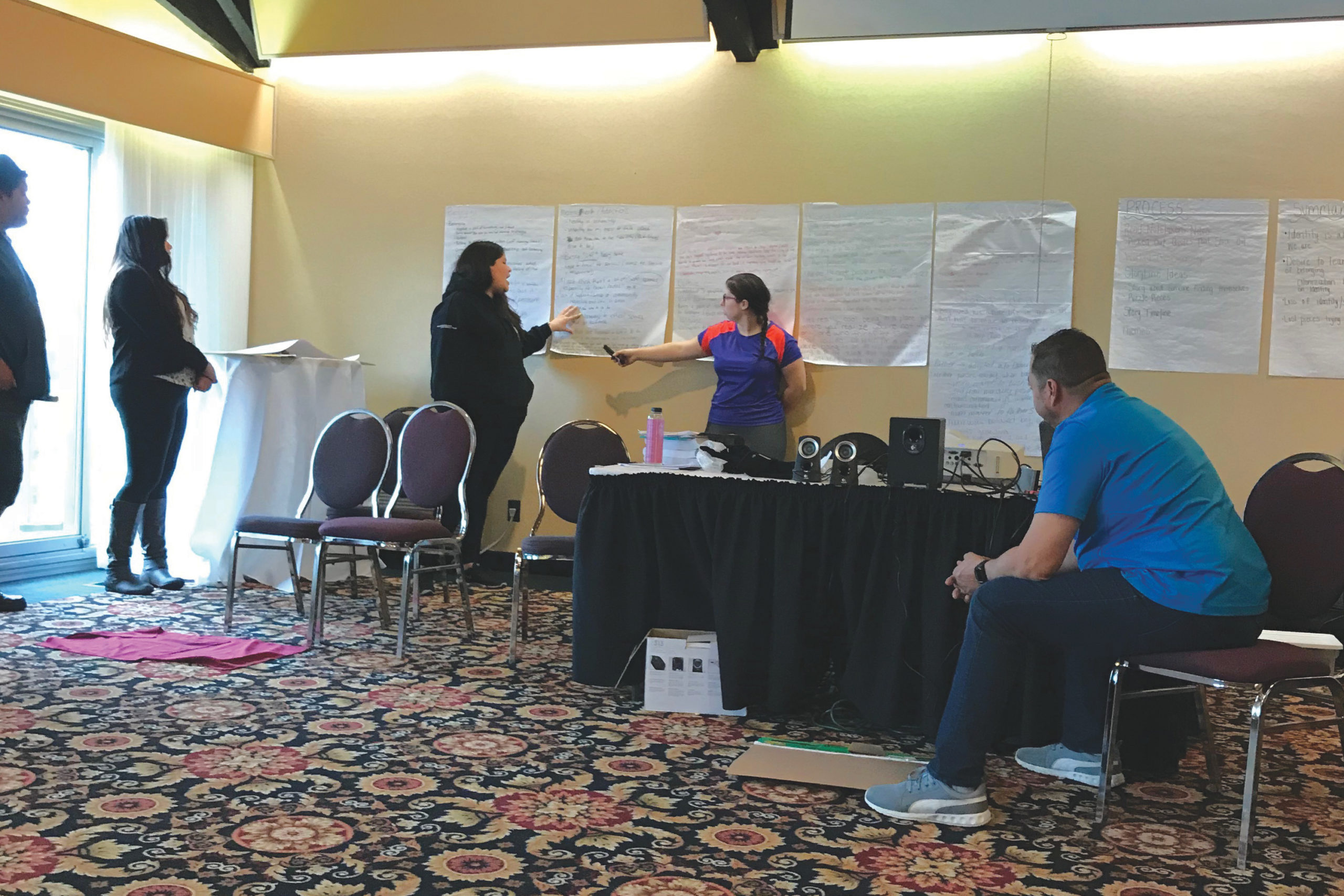 A photo of a group of young advisors presenting the findings of their work. Two advisors stand in front of several chart papers taped to the wall. One of them is pointing to an area of the paper while another one talks. Three other people stand in front of them, listening attentively.