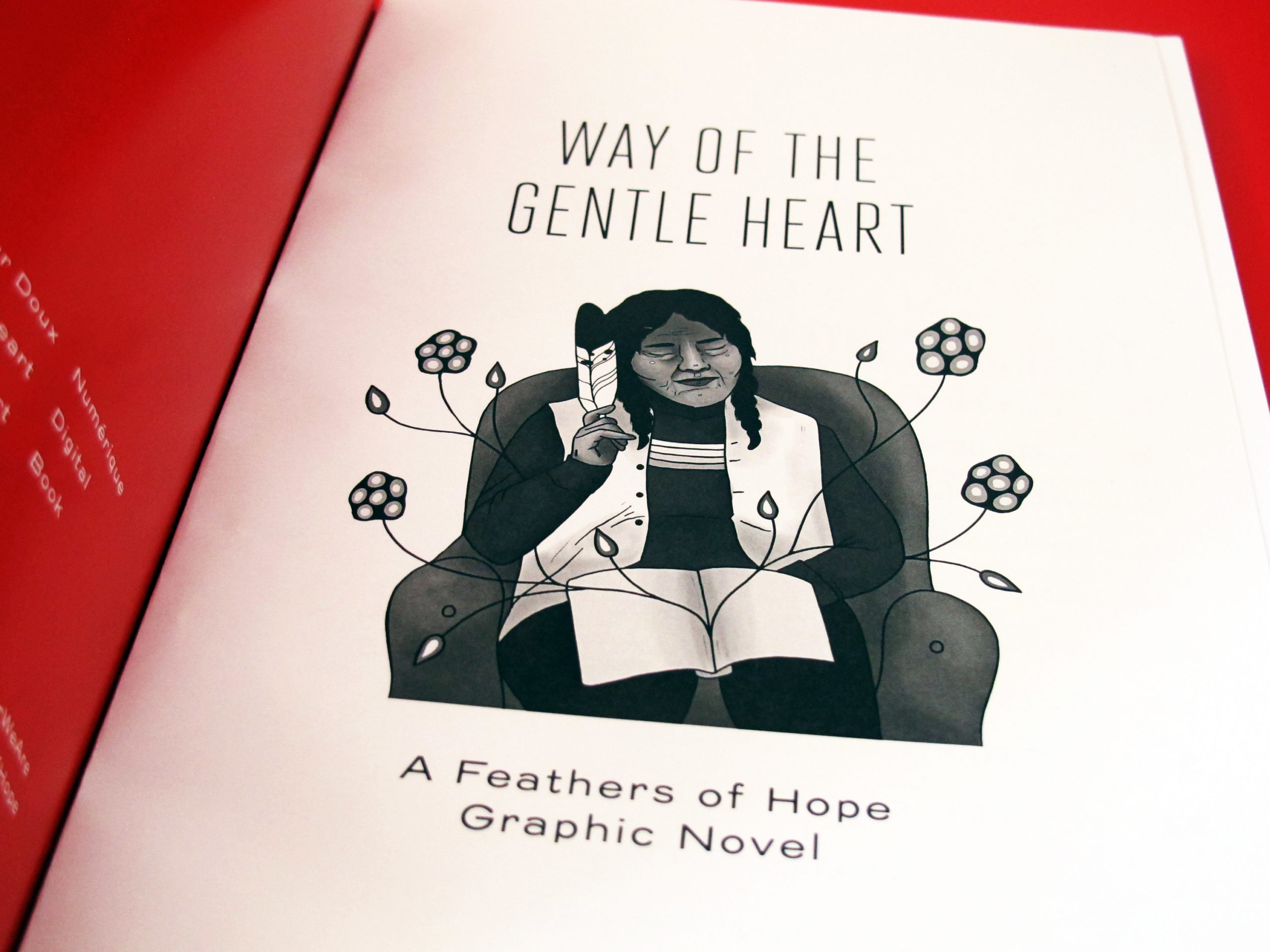 Photo of the opening page to the graphic novel Way of the Gentle Heart. It is a black and white illustration of an Elder sitting on a couch, holding a feather. Their eyes are closed, and their expression is one of complete peace and tranquility. There is an open notebook in the Elder's lap—from its pages are blossoming a series of undulating flowers.