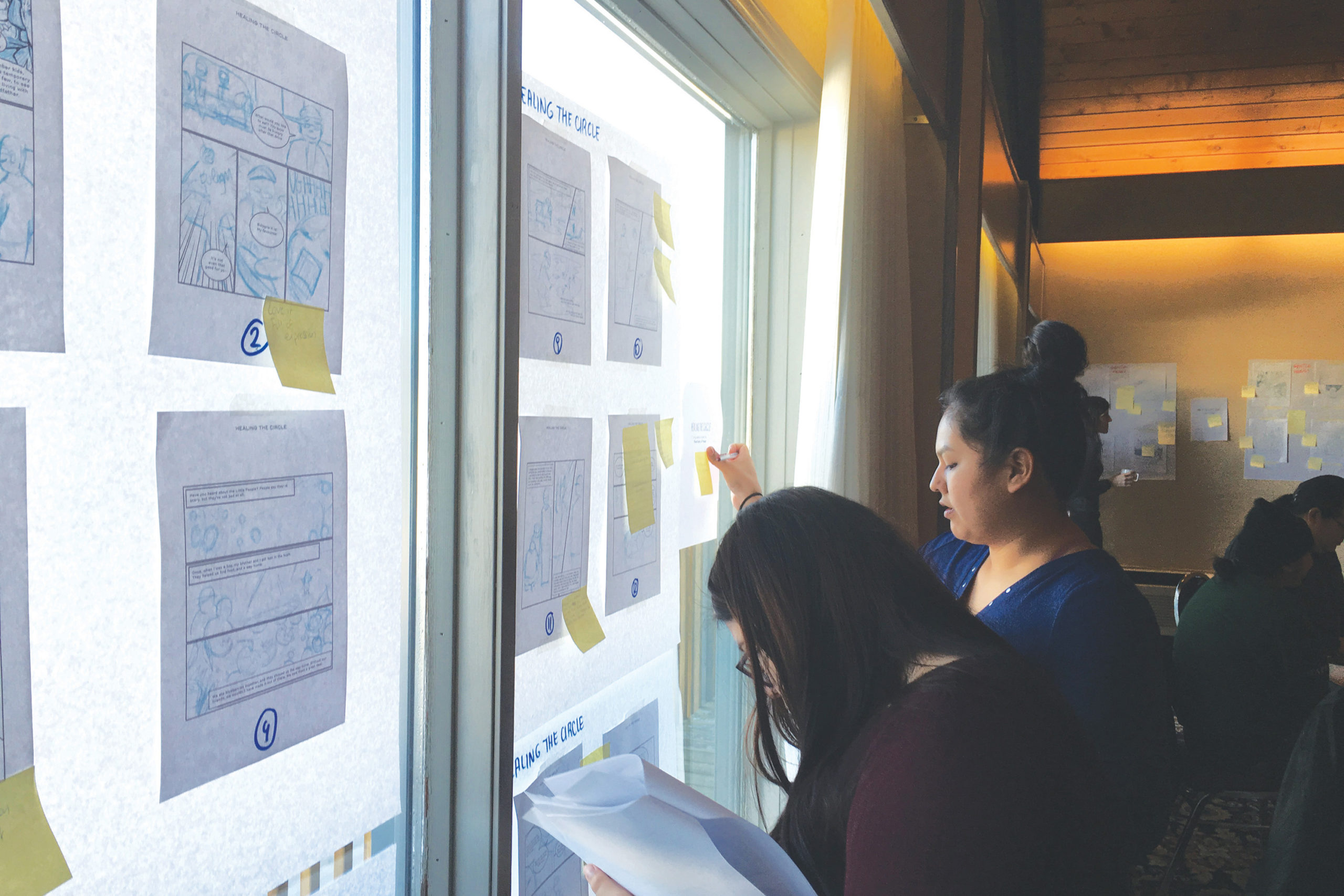 Photo of two young advisors standing in front of a window, to which are taped several graphic novel storyboards. The advisors are giving feedback by placing post-its on individual panels.