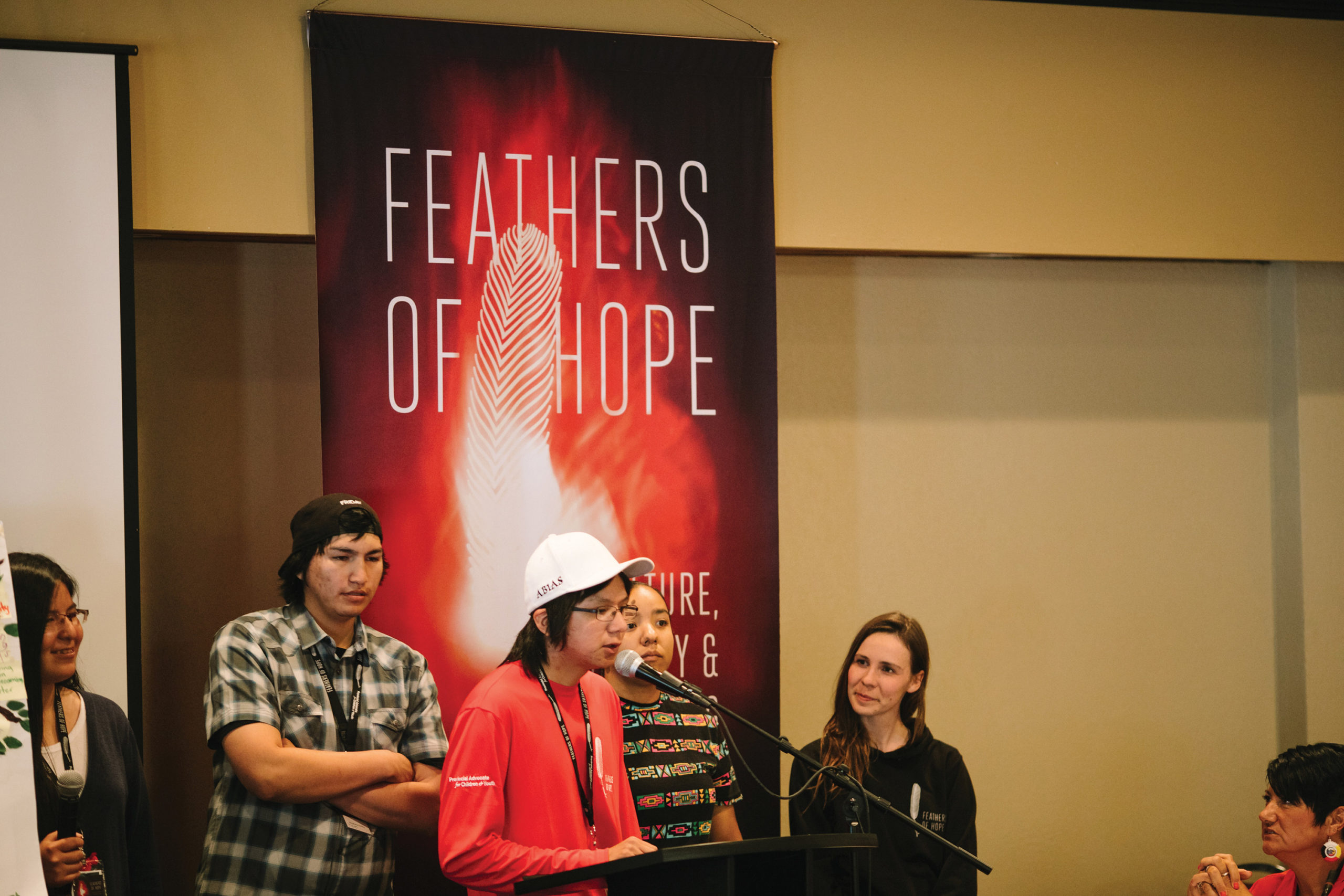 Photo of five young people standing in front of a large, red banner that reads 'Feathers of Hope.' One of them is kneeling over a black stand while they speak over a microphone. The remaining four stand behind, looking determined and strong.