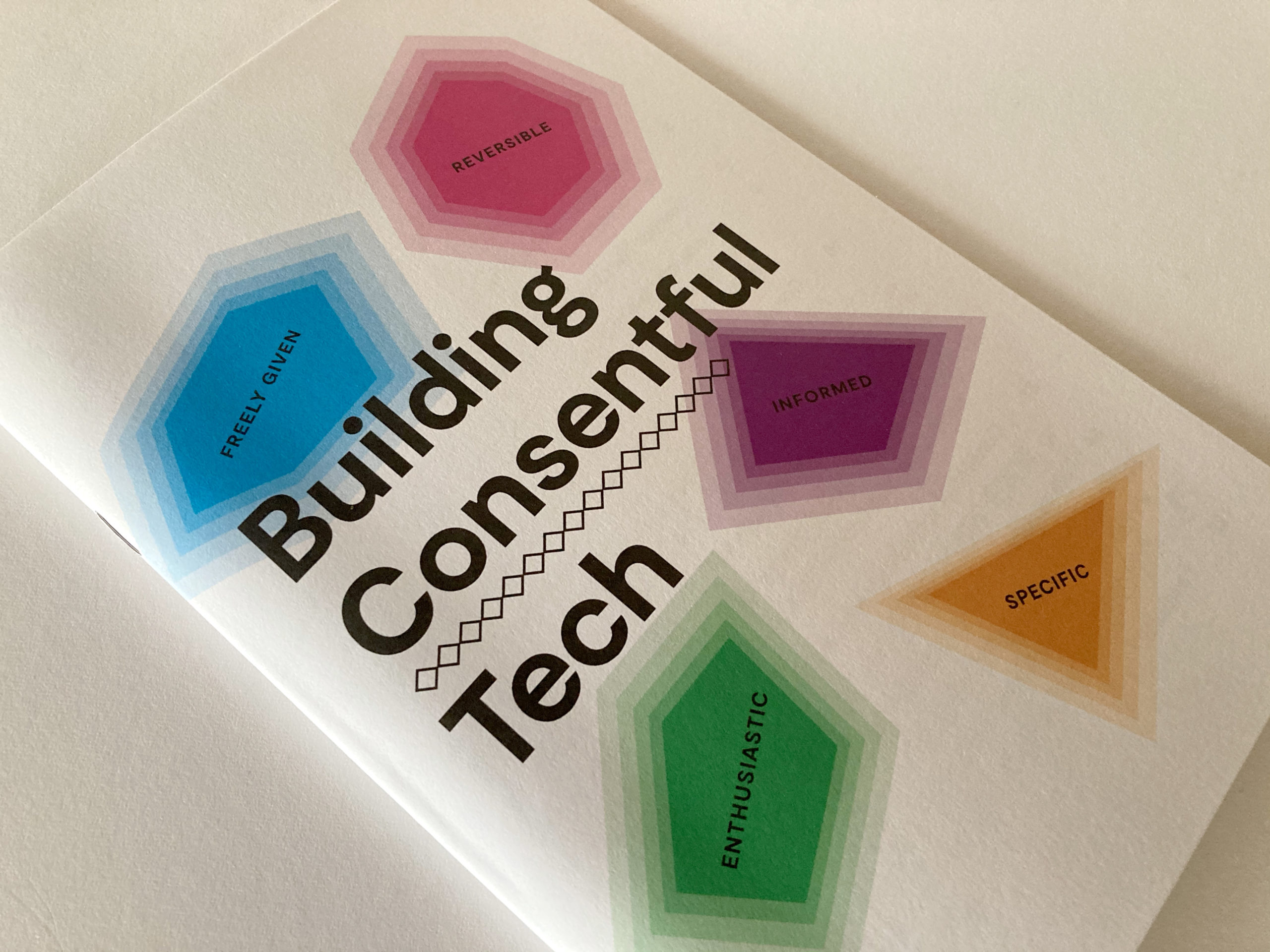 "Cover of the Building Consentful Tech zine. The title is surrounded by gem shapes of different colors, with the words ""Freely Given, Reversible, Informed, Enthusiastic, and Specific"" inside of them."