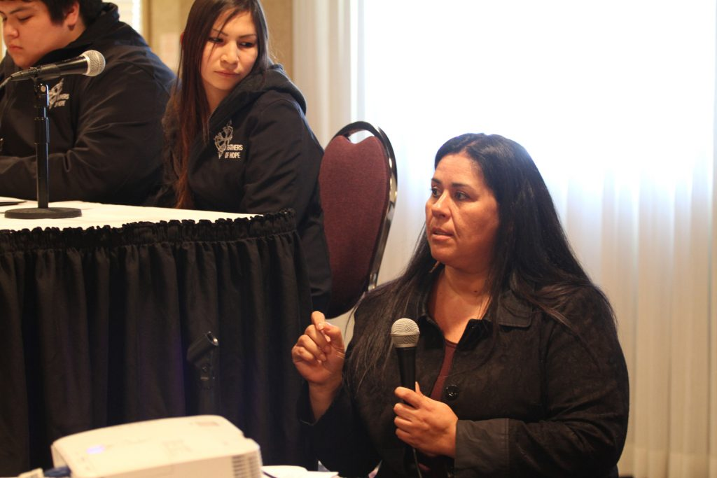 Photo of Laura Arndt speaking at a Feathers of Hope youth forum. Laura is holding a microphone and speaking up as some youth sit listening to her in the background.